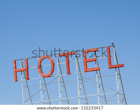 Red neon hotel sign against blue sky.