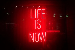 Red neon sign life is now. Glow quote about live and self motivation. Here and now abstract concept.