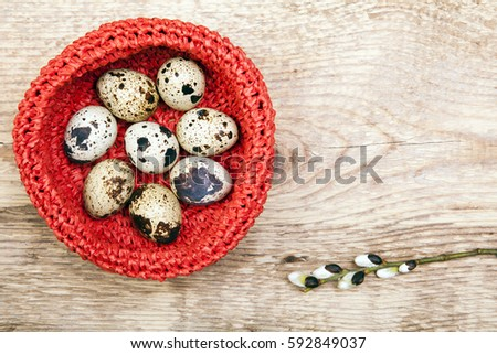 Red nest with quail eggs and tree branch with buds. Easter composition on a wooden background.  #592849037
