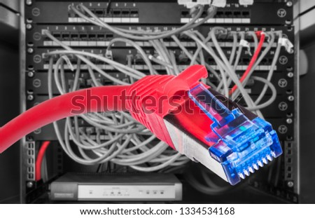 Red network STP-FTP cable with RJ-45 connector close-up. Structured cabling. Power cables plugged in patch panels of black and white computer rack. Blur networking hardware. Digital data transmission. #1334534168