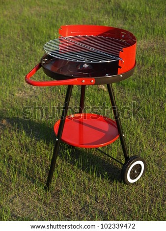 Red new barbecue on grass in garden - stock photo