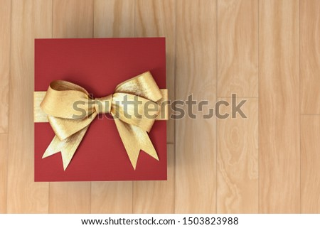 Red new year or Christmas gift box with golden ribbon for celebration concept on wooden board. with empty space for text and design, 3d illustration with clipping mask.