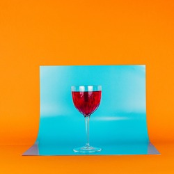 Red Nick and Nora cocktail in orange blue background