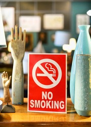Red No Smoking sign with pictorial crossed through cigarette icon in a store or shop warning that it is a smoke free zone and smoking is forbidden