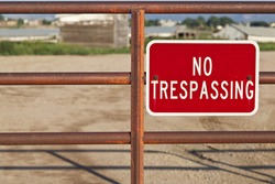 red no trespassing sign on an iron gate with out of focus farm building behind