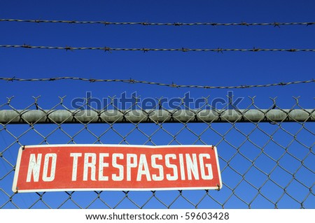 "Red "" NO TRESPASSING"" warning sign on chain link fence"