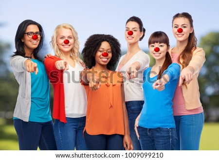 red nose day, diversity and people concept - international group of happy smiling different women with clown noses pointing finger at you over natural background