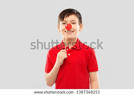 red nose day, photo booth and childhood concept - smiling little boy in polo t-shirt with clown nose over grey background