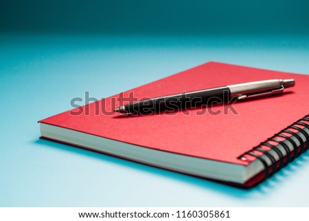 Red notebook and pen on blue table background, Concept for Learning