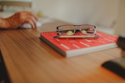 red notebook on a wooden table with a gold pen and a pair of black glasses on it and next to it a man working on his computer clicking the mouse with his right hand with a blurred background