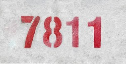 Red Number 7811 on the white wall. Spray paint. Number seven thousand eight hundred and eleven.