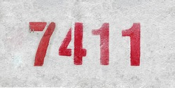Red Number 7411 on the white wall. Spray paint. Number seven thousand four hundred and eleven.