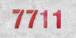 Red Number 7711 on the white wall. Spray paint. Number seven thousand seven hundred and eleven.