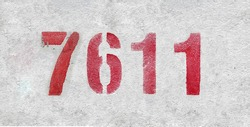Red Number 7611 on the white wall. Spray paint. Number seven thousand six hundred and eleven.