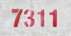 Red Number 7311 on the white wall. Spray paint. Number seven thousand three hundred and eleven.