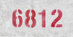 Red Number 6812 on the white wall. Spray paint. Number six thousand eight hundred and eleven.