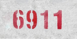 Red Number 6911 on the white wall. Spray paint. Number six thousand nine hundred and eleven.