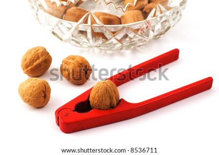 Red nutcracker with walnuts and glass bowl isolated on white with shallow depth of field - stock photo