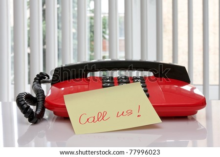 "red office telephone with paper reminder ""call us!"""