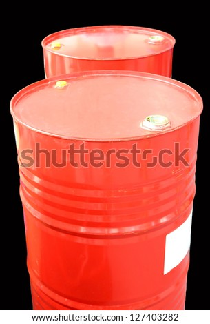 Red oil barrels isolated on black background.