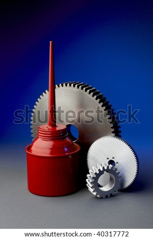 Red oil can with 3 steel gears shot on blue background
