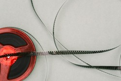 Red old film reel on a green background. 16mm film reel. Filmstrip top view. Flat lay