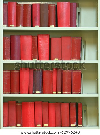red old hardcover books on bookshelf in library