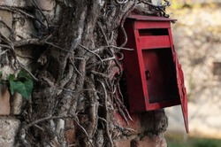Red old mailbox on the wall. Letter boxes
