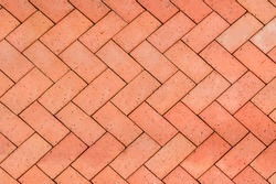 Red-Orange bricks tiled floor with zigzag pattern texture background.
