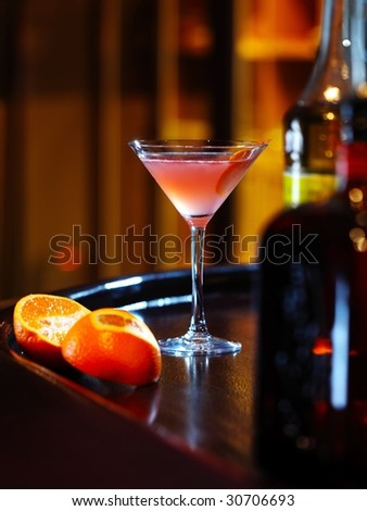 red orange cocktail with orange near the bottle on the wooden bar