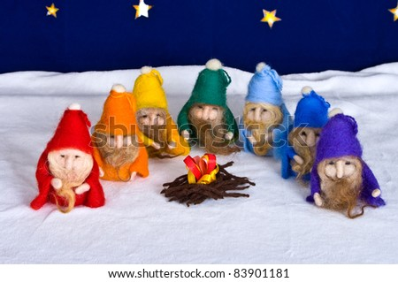 Red,orange,yellow,blue,light-blue,green and volet dwarfs sitting near the fire