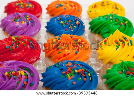 Red, orange, yellow, green and purple cupcakes with sprinkles
