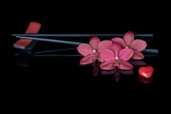 Red orchids flowers phalaenopsis Buddha's Treasure with heart and chopsticks on black glass.