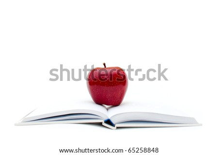 red organic apple placed on the top of the white books
