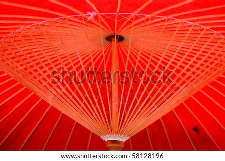 Red oriental paper umbrella open in bright sunlight