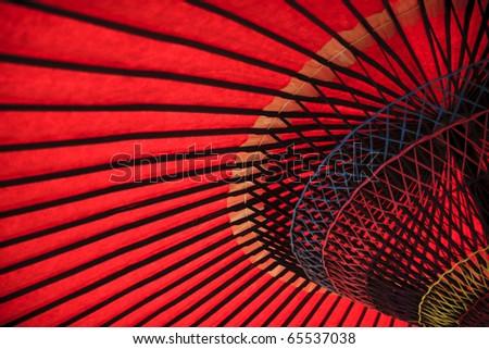 Red oriental paper umbrella open in bright sunlight