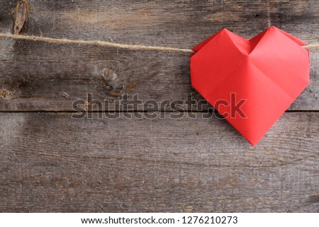 Red origami heart on rope over wooden background, Valentines day concept, copy space for text Stockfoto ©