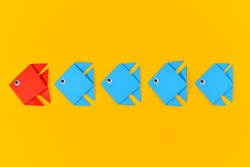 Red origami paper fish swimming in front of rows of blue fish on yellow background. Concept for discovery and strong leadership