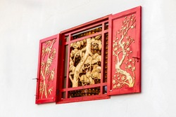 Red ornamented window at Thean Hou Temple, Kuala Lumpur, Malaysia. Chinese temple window decorated with golden motifs of pine, bamboo, and plum. Wooden relief of the Three Friends of Winter.