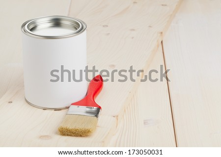 Red paint brush with paint bucket on wooden planks - home renovation or diy concept