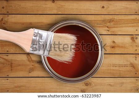red paint can with brush on wooden floor