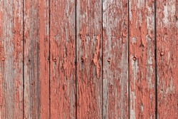 Red paint peeling off of old wooden boards on the side of a barn texture