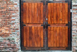 Red painted wooden barn door and window in old brick wall