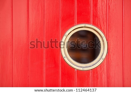 red painted wooden door with a porthole