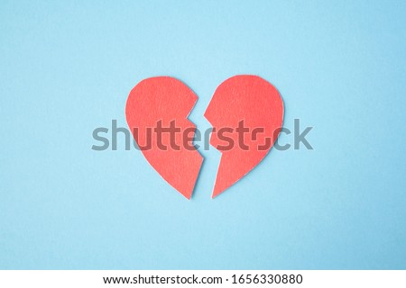 Red paper broken heart on bright background. Divorce, parting, therapy, love, psychologist, family ruined concept