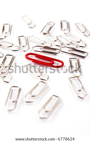 Red paper clip among a heap of metal paper clips