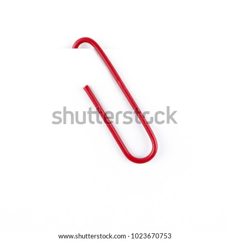 Red paper clip isolated on white background. Close up and top view.