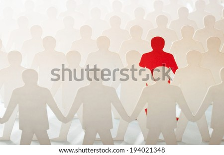 Red paper cut-out figure standing out among other white paper cuts