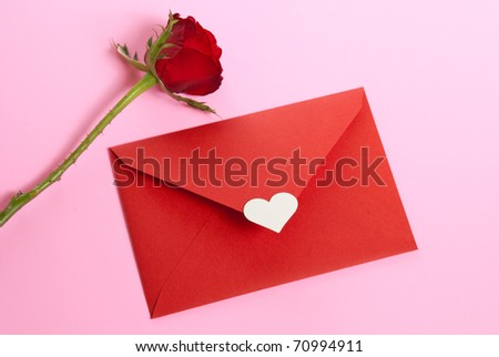 red paper envelope with white heart and red rose on pink background