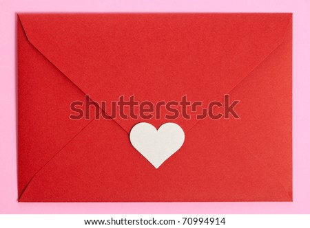 red paper envelope with white heart on pink background